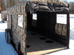 The back door rolls up easily and secures to the top. This Trailer has six fishing holes installed.